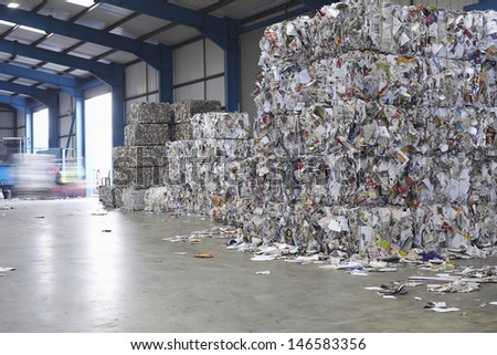 Compacted piles of paperwaste at recycling plant - stock photo