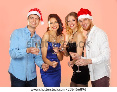 company enjoys Christmas.  Portrait of modern young people enjoying themselves at Christmas party. Company of friends in Santa caps holding flutes in hands - stock photo