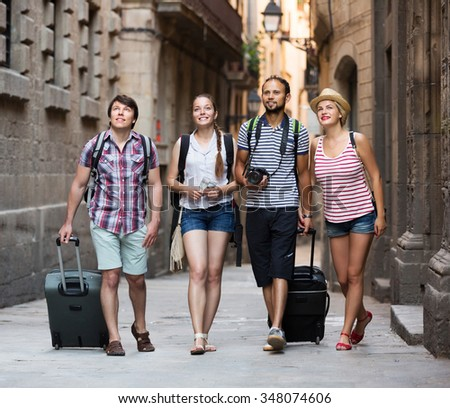 Company of active travelers with travel bags walking the city - stock photo