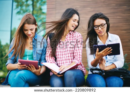 Company of attractive teenage girls reading outside - stock photo