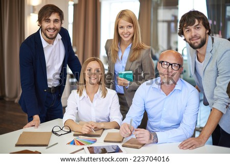 Company of elegant designers looking at camera in office - stock photo