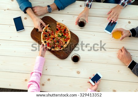 Company of friends different sex sitting at street cafe wooden table drinking aperitifs cocktails Eating Pizza  mobile telephones top view - stock photo