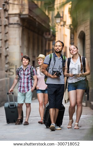 Company of happy active travelers with travel bags walking the city - stock photo