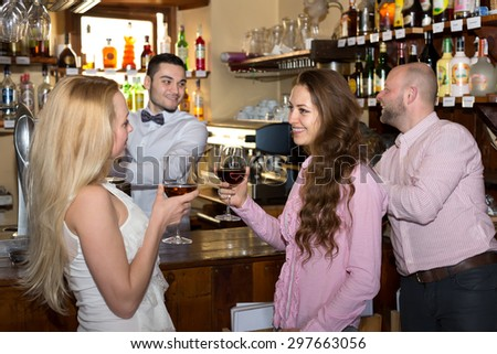 Company of people at a bar: two beautiful women drinking wine while bartender is pouring beer fo a man