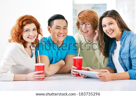 Company of smart groupmates sitting by the table and having break after lesson - stock photo
