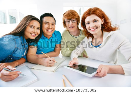 Company of smart groupmates sitting by the table and looking at camera - stock photo