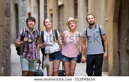 Company of smiling travelers with travel bags walking the city - stock photo