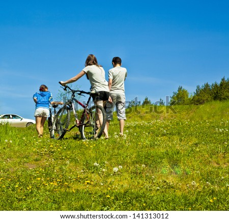 company of three teenagers goes backs after a walk to the car on a background summer lawn and blue sky - stock photo