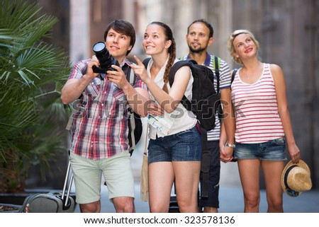 Company of young american travelers taking shots during city walking - stock photo