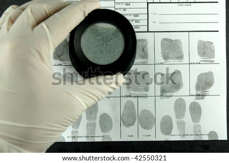 compare the fingerprint through the  magnifier glass - stock photo