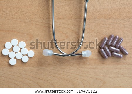 Comparing many pills of conventional or modern medicine versus many capsule of traditional,alternative, herbal elderberry medicine on wooden background with doctor medical stethoscope.