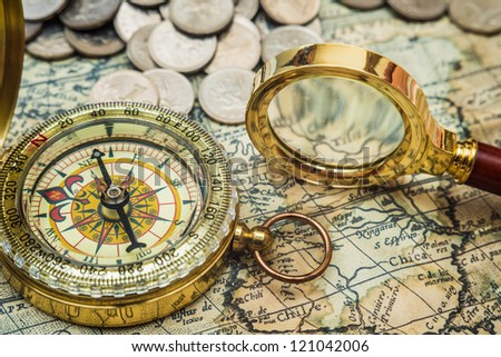 compass and magnifying glass gold color on the old map with coins - stock photo