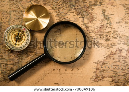 Compass and Magnifying glass on the vintage map for traveling concept