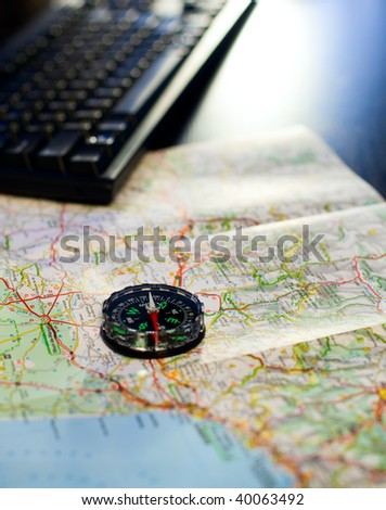 Compass and map on a table with  keyboard, very shallow DOF - stock photo