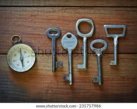 Compass and old keys on a wooden surface   - stock photo