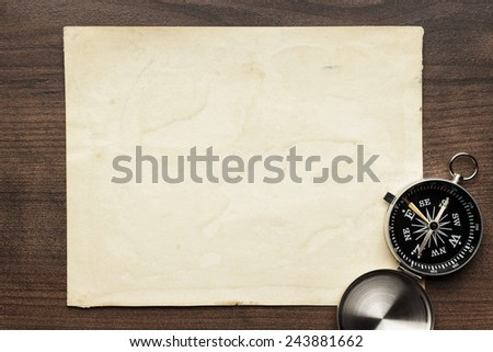 compass and old paper on the brown wooden table background - stock photo