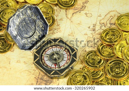 compass and pirate golden coin on a old world map - stock photo