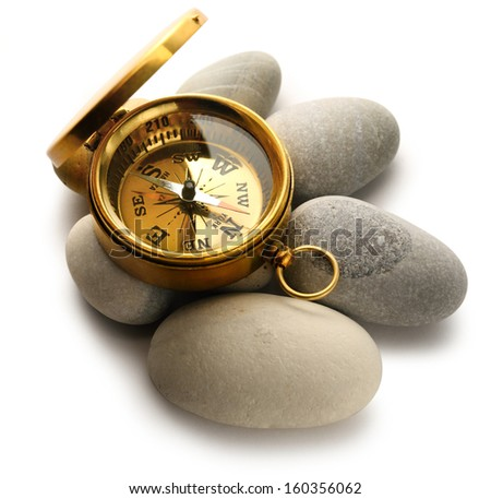 Compass and sea stones on white - stock photo