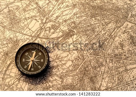 Compass and terrestrial globe on old map - stock photo