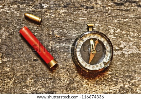 Compass and two bullets on old wooden background - stock photo
