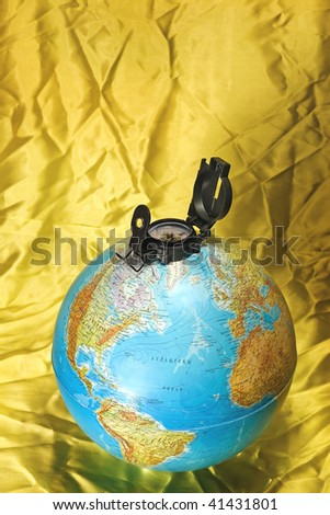 Compass at top of the globe on wrinkled yellow textile - stock photo