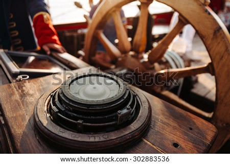 compass close-up and driving on the old wooden ship with red sails - stock photo