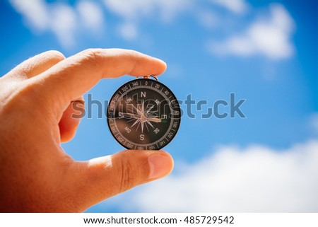 Compass in hand on sky background.