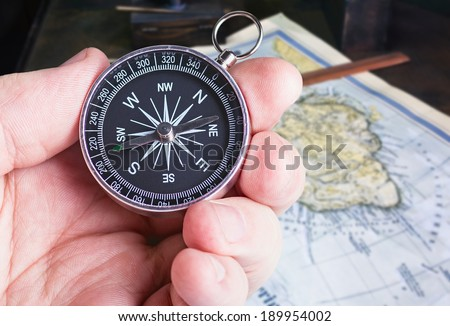 compass in hand paves the route map  - stock photo