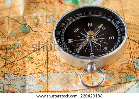 Compass laying on an orienteering map - stock photo