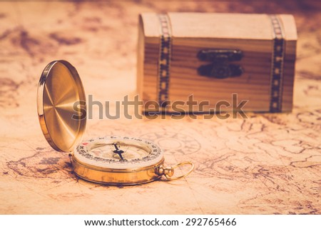 compass lying on vintage map with treasure chest. Vintage filter. - stock photo