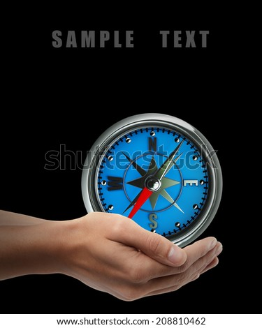 Compass. Man hand holding object  isolated on black background. High resolution  - stock photo