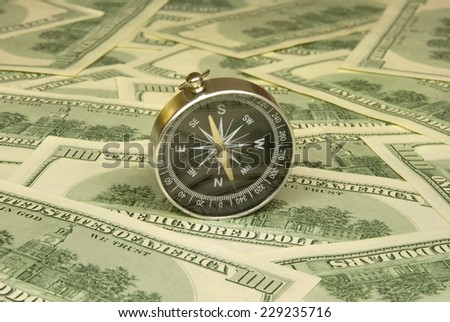 Compass on a background of dollars (it is a lot of money). - stock photo