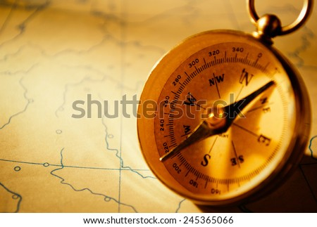 Compass on a map background in yellow tinting