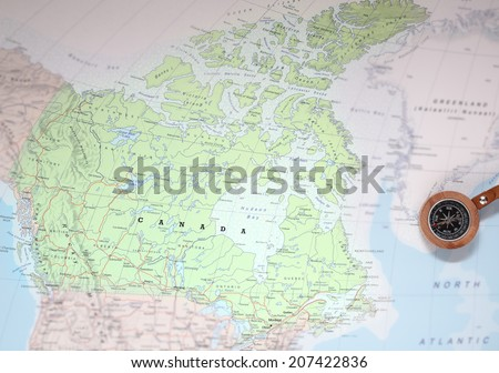 Compass on a map pointing at Canada and planning a travel destination - stock photo
