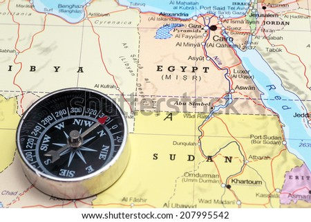 Compass on a map pointing at Egypt, planning a travel destination - stock photo
