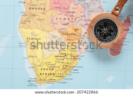 Compass on a map pointing at South Africa and planning a travel destination - stock photo