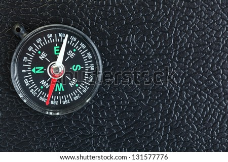 compass on black leather background - stock photo