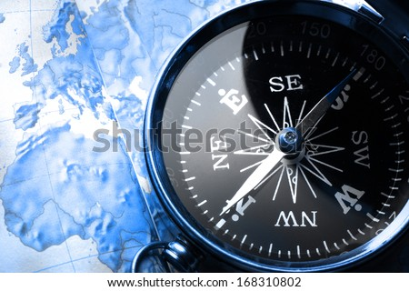 Compass on map background in blue toning - stock photo