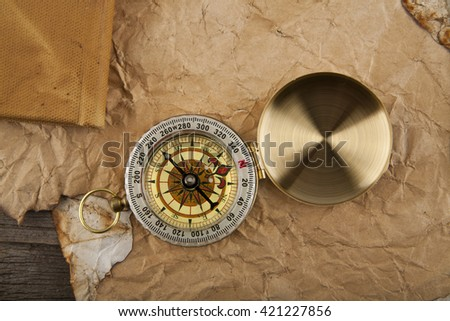 compass on old paper on wooden background closeup