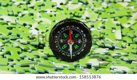 compass on pile of green puzzle - stock photo