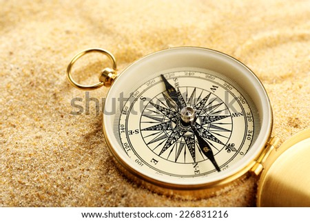 Compass on sand close-up - stock photo