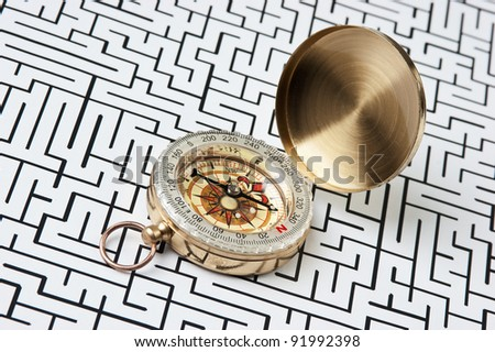 compass on the background of the labyrinth - stock photo