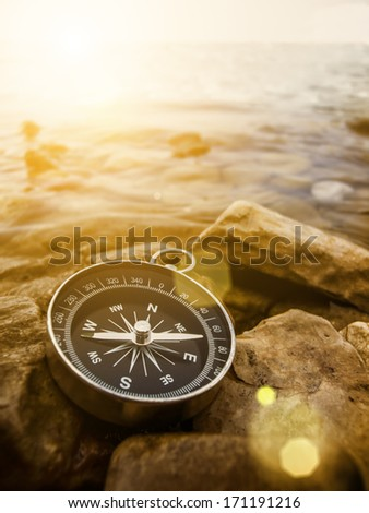 compass on the bank with sunflare - stock photo