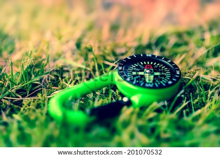 Compass on the grass close up outdoors concept - stock photo