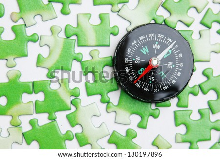 compass on the green puzzle - stock photo