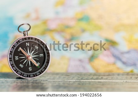 compass on the table against the background of a tourist map. Focus on the compass needle