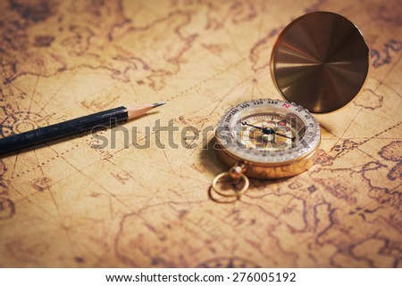 compass on vintage map with pencil. - stock photo