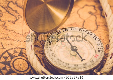 Compass on vintage map with rope. Vintage filter. - stock photo