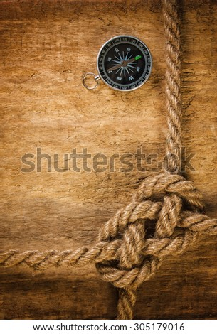 Compass with a rope on the background of the old board - stock photo