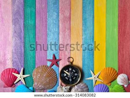 compass with sea shells on a colored wooden background - stock photo